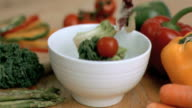 Vegetables falling into bowl in super slow motion