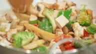 Groenten bakken in de pan en geroerd met een houten lepel