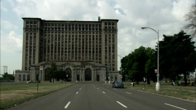 A vehicle drives through Roosevelt Park towards the tattered facade of the Michigan Central Train Station. Available in HD.