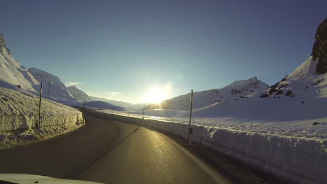 Fahrzeug POV fahren auf verschneite Straße bei Sonnenuntergang