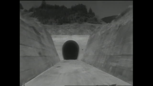 A vehicle enters an unlighted tunnel.