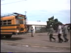 A vehicle passes buses and boys at a stop light selling cold water from plastic bags on the outskirts of Managua Nicaragua in 1999 They say over and...