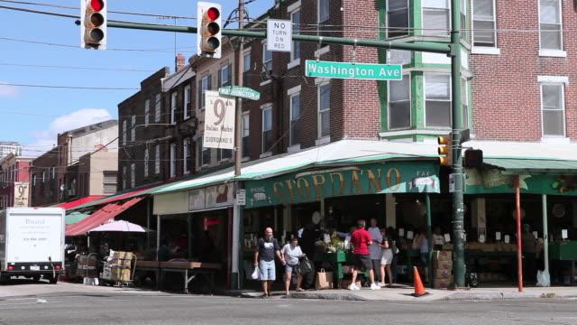 WS Vehicle traffic passing through intersection near 9th Street Italian Market / Philadelphia, Pennsylvania, United States
