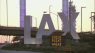MS Vehicle traffic traveling past LAX airport sign / Los Angeles, California, United States