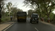 Vehicles overtake one another on a busy rural road.