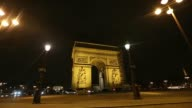 Vehicles pass in front of the Arc de Triomphe national monument at night in Paris France on Tuesday Feb 18 A sign for Place Charles de Gaulle stands...