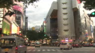Vehicles pass pedestrians at a crosswalk at Dogenzaka-shita crossing in Tokyo.