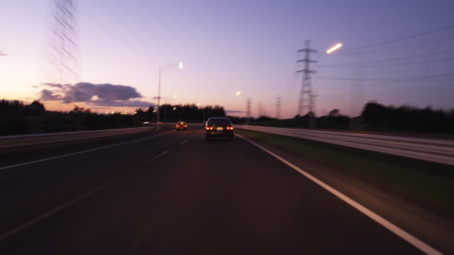 T/L POV Vehicles passing through road at dusk / Auckland, New Zealand.