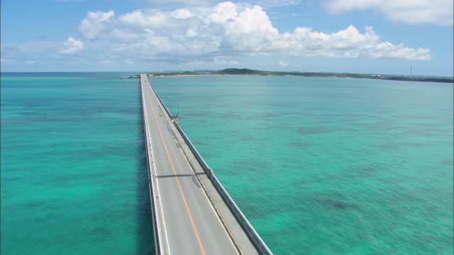 WS ZI POV AERIAL Vehicles passing through Straight road on ocean / Okinawa, Japan