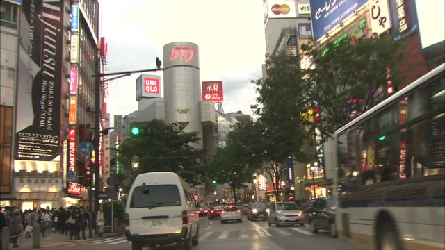 Vehicles use their headlights as they travel on Dogenzaka Street.