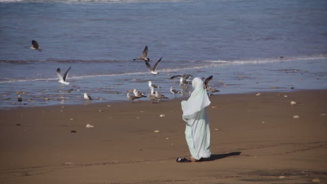 Veiled woman on beach