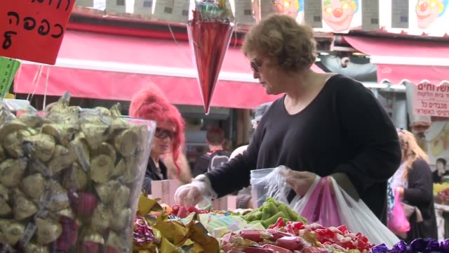 Vendor and customers interact at candy market in Tel Aviv's largest marketplace