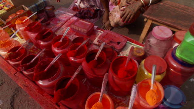 A vendor sells colored powders or spices.
