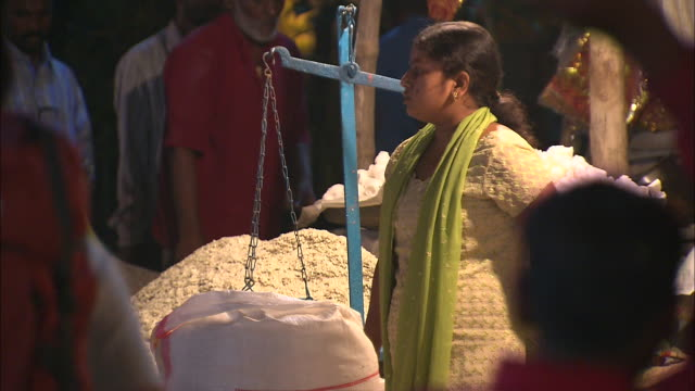A vendor sells grain at a busy marketplace in India.