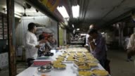 Vendors talk with customers at a grain store at the Vashi Agricultural Produce Market Committee wholesale market in Mumbai India on Monday Aug 12...