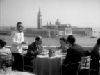 VENICE ITALY CU 'Venice Lido' poster w/ building winged lion flag TERRAZZA DANIELI PAN Open air hotel rooftop dining terrace w/ male waiters waiting...