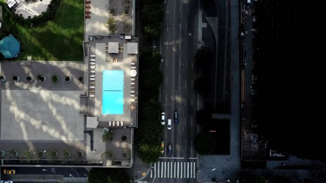 vertical shot of pool area, forward slide with tilt up to see the cityscape
