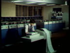 Very large dated computers and printers people working at them; 1980s