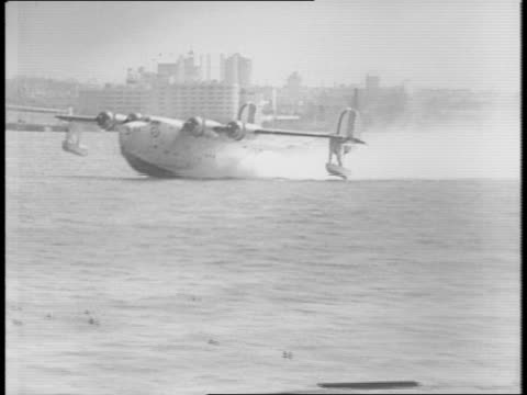 A very large plane with four engines is led out of its hanger by a ground crew / the plane rolls of a short pier and into the water / the plane's...