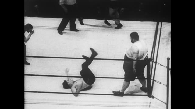 / very overweight man wrestles with two smaller men as audience watches / four men try to fight the larger man / overweight wrestler takes a leap at...