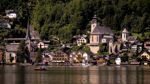 Vew of Hallstatt from across the Lake with tourist self drive rental boat