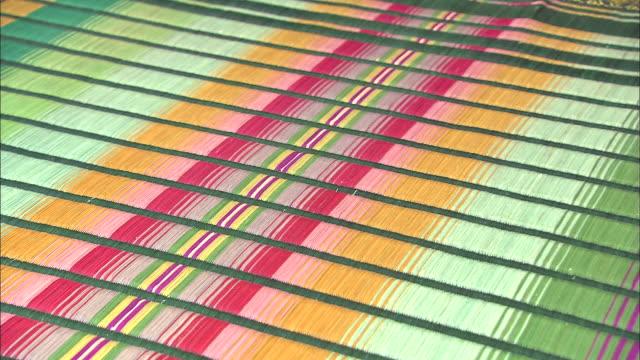 Vibrant colors adorn a rush mat.