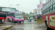 WS Vibrant decorated bus arriving and parking at bus station, pedestrians walking in rain / Chidambaram, Tamil Nadu, India