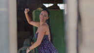 SLO MO. Vibrant woman dances alone and smiles at camera in rustic barn setting.