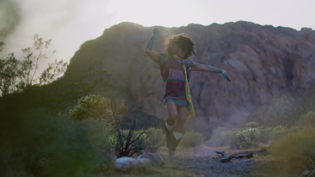SLO MO. Vibrant young woman dances in a cloud of dust in a wild desert landscape.