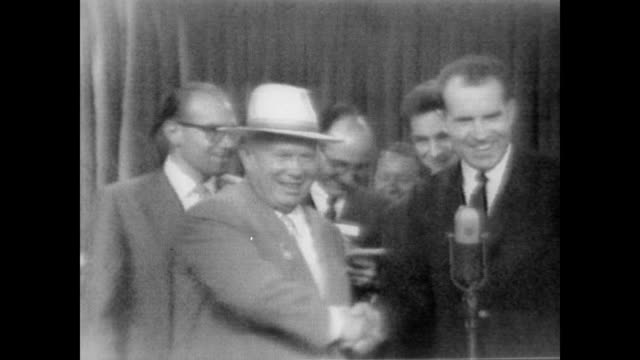 / Vice President Richard Nixon and Soviet chief Nikita Khrushchev debate standing next to a microphone and using interpreters / conversation is light...