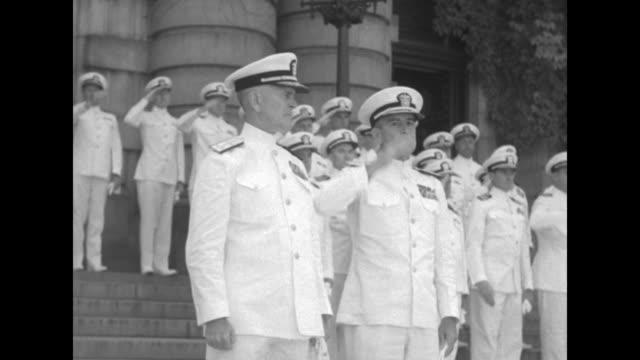 ViceAdm Harry Hill on left and Adm C Turner Joy on right walking across courtyard past formation of midshipmen / two overhead shots of midshipmen...
