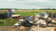 Victims talk beside a pile of debris and devastation left behind from tornado