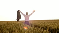 SLO MO Victorious businessman punching the air in a field