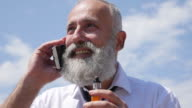 4K Video - Business. A bearded senior businessman with e-cigarette  speaks on the phone.