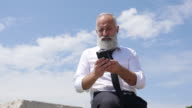 4K Video - Business. A bearded senior businessman writes a message over the phone.