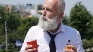 4K Video - Business. Bearded senior businessman drinks coffee and smoking an e-cigarette