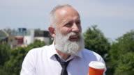 4K Video - Business. Bearded senior businessman drinks coffee