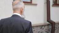 4K Video - Business. Gray-haired bearded businessman happy meeting in town