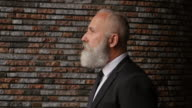 4K Video - Business. Gray-haired bearded businessman is walking in the city