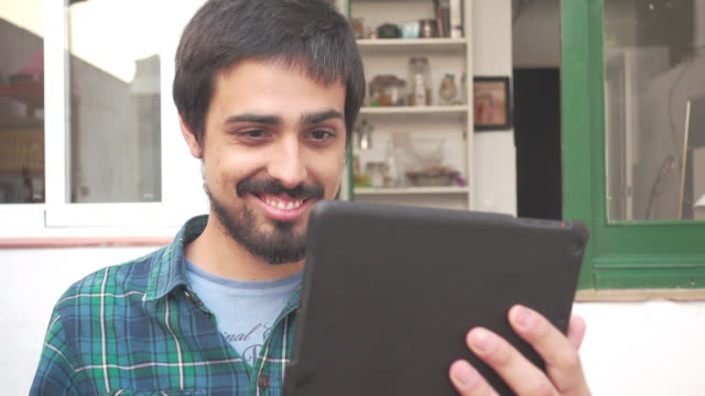4K | Video call by digital tablet. Young man with beard uses ipad to talk by Skype with a friend or family. Frontal close up shot. He smiles and is expressive during the communication voice over IP. He is outdoors at an old yard of a home.