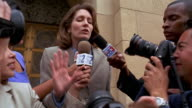 Video camera point of view low angle medium shot woman in suit speaking / surrounded by press