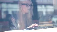 video-clip, die durch ein Fenster von coffeshop von Frau arbeitet auf einem laptop