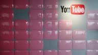 Video creators walk past Google Inc YouTube logo displayed at the company YouTube Space studio in Tokyo Japan Google's YouTube Space studio in Tokyo...