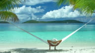 video of a woman swinging in hammock at the beach
