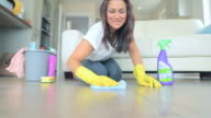Video of brunette woman scrubbing the living room floor