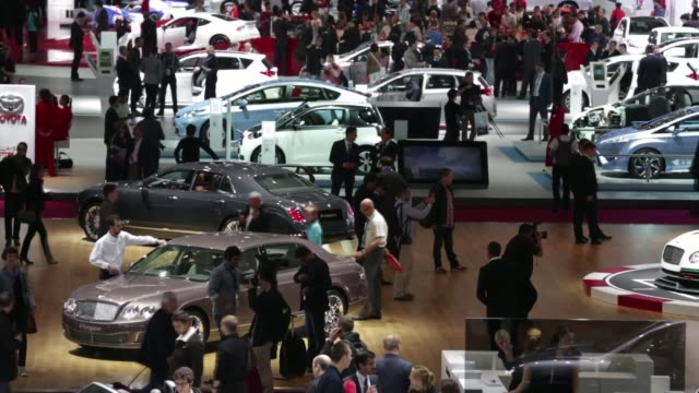 video of cars on display / expo center crowded with vistors looking at automobiles Paris Auto Show Wide Shot on September 28 2012 in Paris France