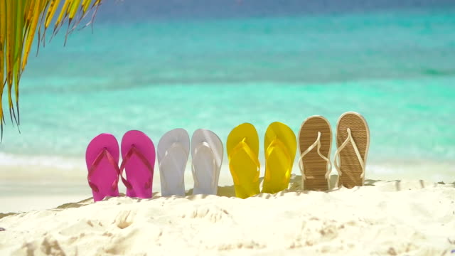 video of colorful sandals in sand on a Caribbean beach