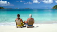 video di coppia in luna di miele seduti in sedie a sdraio in spiaggia