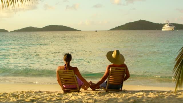 video di coppia in luna di miele a guardare il tramonto in spiaggia caraibica