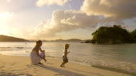 video of mother and child playing on a Caribbean beach